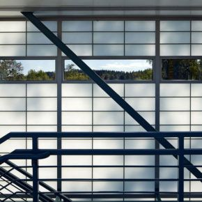Staircase along side large wall of commercial glass windows