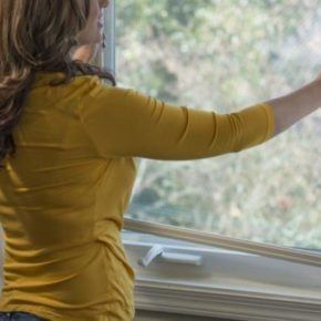 woman installing new screen on residential window