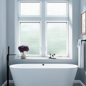 bath tub next to two large residential glass windows