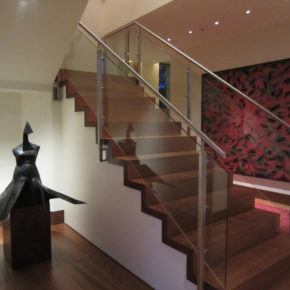 residential staircase leading up to second floor with glass handrails