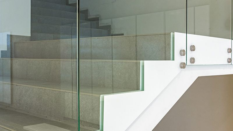 view of stairs with glass handrail system