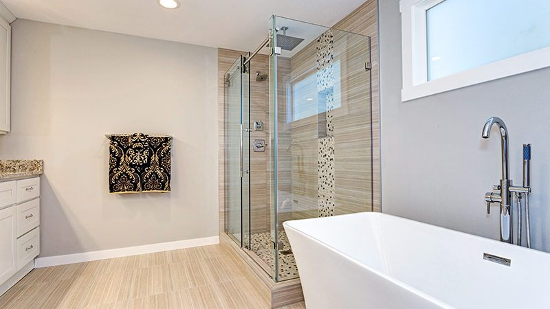 bathroom with white bathroom and heavy glass shower enclosure