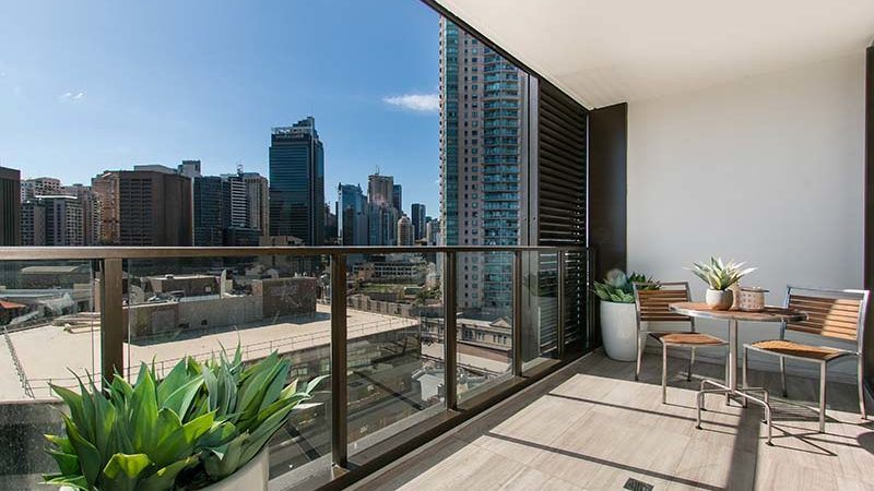 Modern balcony with a clear glass railing overlooking a beautiful city view